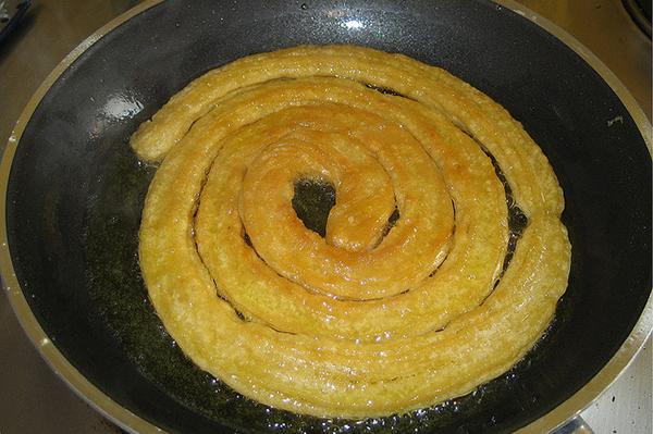 При жарке пончики заворачивают в спираль.