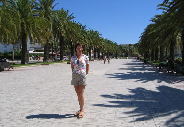Девушка на пальмовой аллее.
